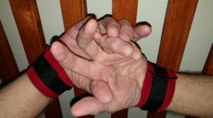 man's hands cuffed to headboard slats