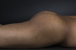 photo of a man lying face-down, showcasing buttocks and thighs
