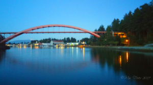 bridge at night with reflections of light on water beneath
