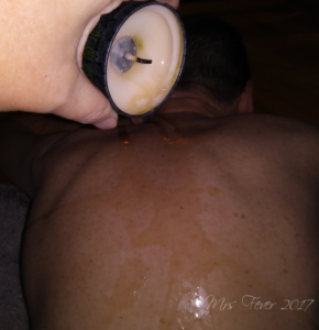 pouring Shunga candle wax on man's back