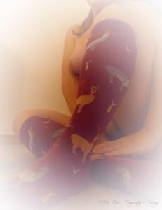 nude woman with knees crossed, wearing llama socks