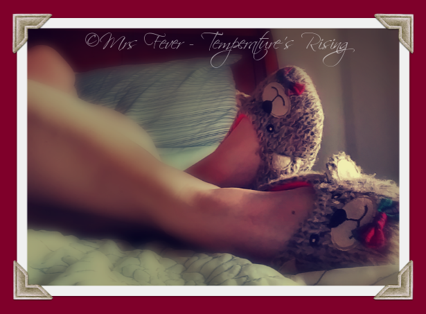 nude woman reclining in bed with bear slippers on feet